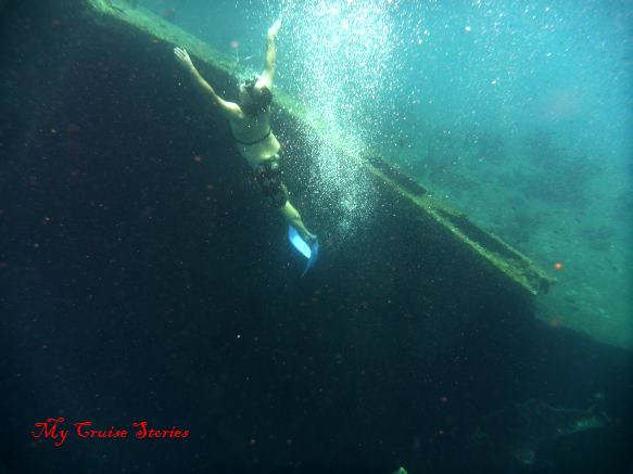 snorkeler diving near shipwreck
